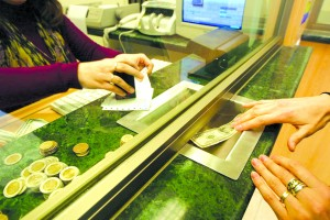 A civilian buys dollar at a currency exchange hous